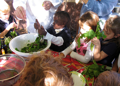 A child helps make the salad before sampling.