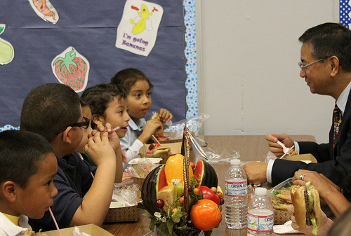 Allen Ng (right), Regional Administrator for Food and Nutrition Service, is having lunch with Columbia School students.