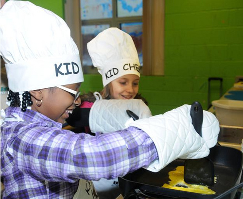 Tanyah Ramos and Caylie Bain scramble eggs in the first step of a healthy fried rice recipe they are learning through the KID CHEF program sponsored by the Food Bank of Delaware.