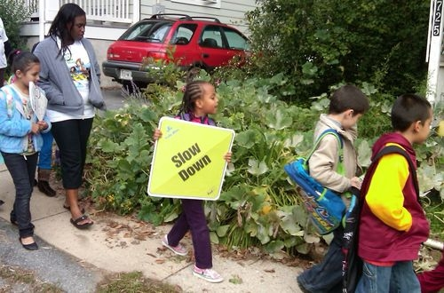 Student holds a sign reading 'slow down' during Walk to School Day