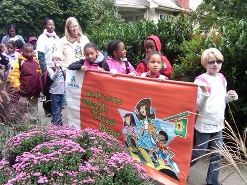Students carry a sign promoting the Safe Routes to School program